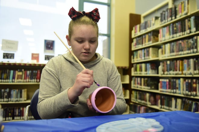 Faith Dyer, 13, of Mansfield, paints a pot into which she will plant cacti Thursday night at the Mansfield Richland County Public Library.