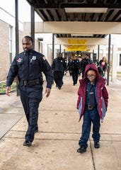 MPD officer Tadario Holmes and 8-year-old Shaheem Young, Jr. head the the police station for a ceremony on  Thursday, Feb. 13, 2020.