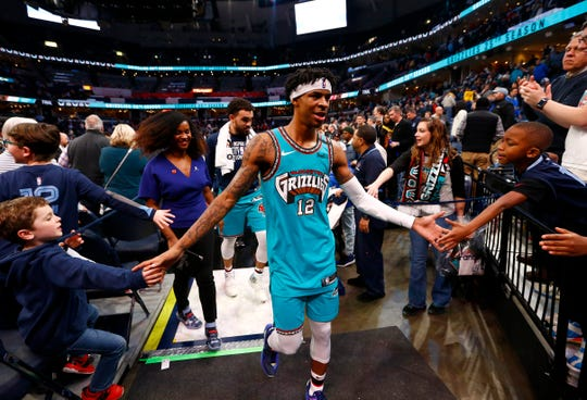 Memphis Grizzlies guard Ja Morant high-fives fans as he leaves the court after their 111-114 win over the Portland Trail Blazers at the FedExForum on Wednesday, February 12, 2020.