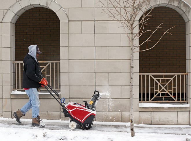 Phillip Curry clears the sidewalk in downtown Wauwatosa near W. State Street and Underwood Ave. on Thursday, Feb. 13, 2020.  According to the National Weather forecast for Milwaukee, temperatures today are only expected in the teens with wind chill between 5 and zero. However, conditions start to warm up just in time for the weekend.