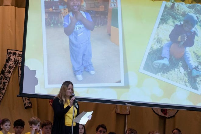 Teacher Amber Mahaffy remembers Jamal Anderson Jr., seen smiling in images above her head, during a memorial Thursday at German Immersion Elementary School in Milwaukee. Jamal died of a gunshot wound Saturday, Feb. 8, 2020.
