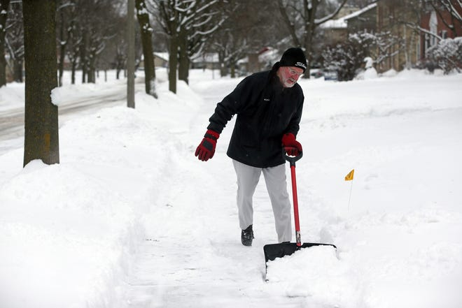 "Jerry Slaske, 68 of Wauwatosa, clears a sidewalk on N. 97th Street on Thursday, Feb. 13, 2020. ""Sure I'd rather it were in the 70 degrees and I was on the golf course, but this is good exercise,"" said Slasek."