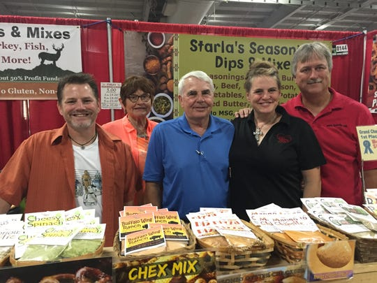 Starla Batzko sells her seasoning mixes from her business, Starla's Seasonings, Dips and Mixes. Here she gets help from her brother, Phil Schlamp, her mother, Kay Schlamp, her father, Del Schlamp and her husband, David Batzko, at a Wisconsin State Fair booth.