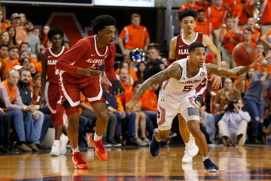 Feb 12, 2020; Auburn, Alabama, USA; Auburn Tigers guard JÕVon McCormick (5)reaches for the ball as Alabama Crimson Tide guard Herbert Jones (1) gives chase during overtime at Auburn Arena. Mandatory Credit: John Reed-USA TODAY Sports