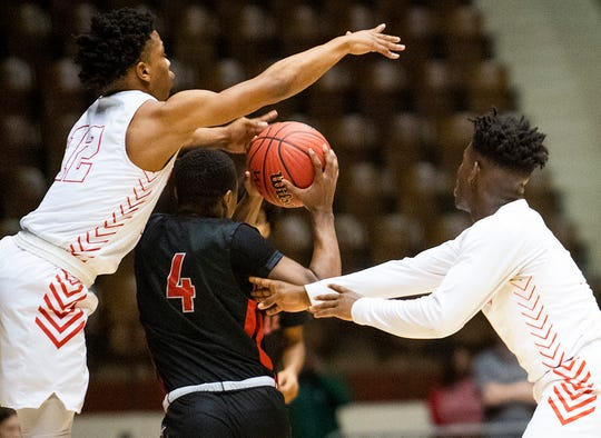 Lee's Jakel Williams (12) and Lee's Nicholas Barnes (11) double team Central-Phenix City's Xavier Carnes (4) in AHSAA Regional action at Garrett Coliseum in Montgomery, Ala., on Thursday February 13, 2020.