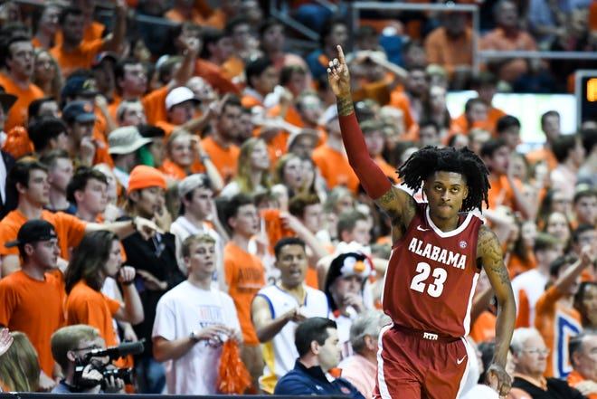 Alabama guard John Petty Jr. (23) celebrates the score that tied Auburn at the end of the second half of an NCAA college basketball game, Wednesday, Feb.12, 2020, in Auburn, Ala. (AP Photo/Julie Bennett)