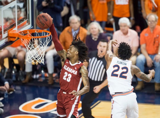 Alabama's John Petty Jr. (23) dunks the ball guarded by Auburn guard Allen Flanigan (22) at Auburn Arena in Auburn, Ala., on Wednesday, Feb. 12, 2020. Auburn leads Alabama 44-41 at halftime.