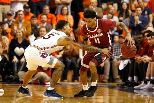 Feb 12, 2020; Auburn, Alabama, USA; Auburn Tigers guard JÕVon McCormick (5) tries to steal the ball from Alabama Crimson Tide guard James Bolden (11) during overtime at Auburn Arena. Mandatory Credit: John Reed-USA TODAY Sports