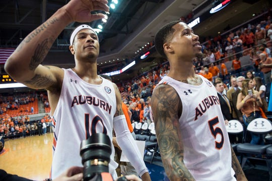Auburn guard Samir Doughty (10) and guard J'Von McCormick (5) high five fans after the game at Auburn Arena in Auburn, Ala., on Wednesday, Feb. 12, 2020. Auburn defeated Alabama 95-91.