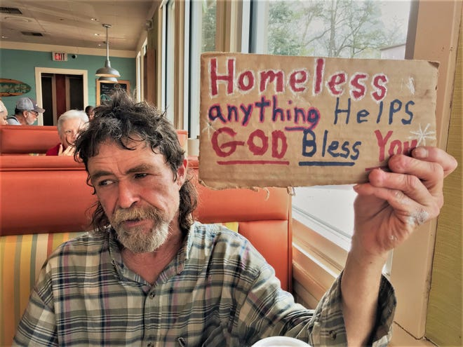 Ricky Vickery, who is a panhandler in Montgomery, holds a sign asking for help.