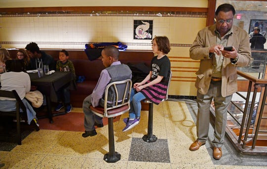 "Vencen Horsley, right,  was a participant in the sit-ins in the 1960s. Horsley checks his phone during a break as Ma""Lique Browder and Norah Mallory sit in original counter chairs at Woolworth on 5th. Fourth graders from Explore! Community School have been studying the desegregation of restaurants and stores in the South.   On Thursday Feb. 13, the exact day the sit-ins began, the students commemorated the 60th anniversary of the demonstrations by visiting and dining at Woolworth on 5th, the site of sit-ins in downtown in Nashville, Tenn. Thursday, Feb. 13, 2020."