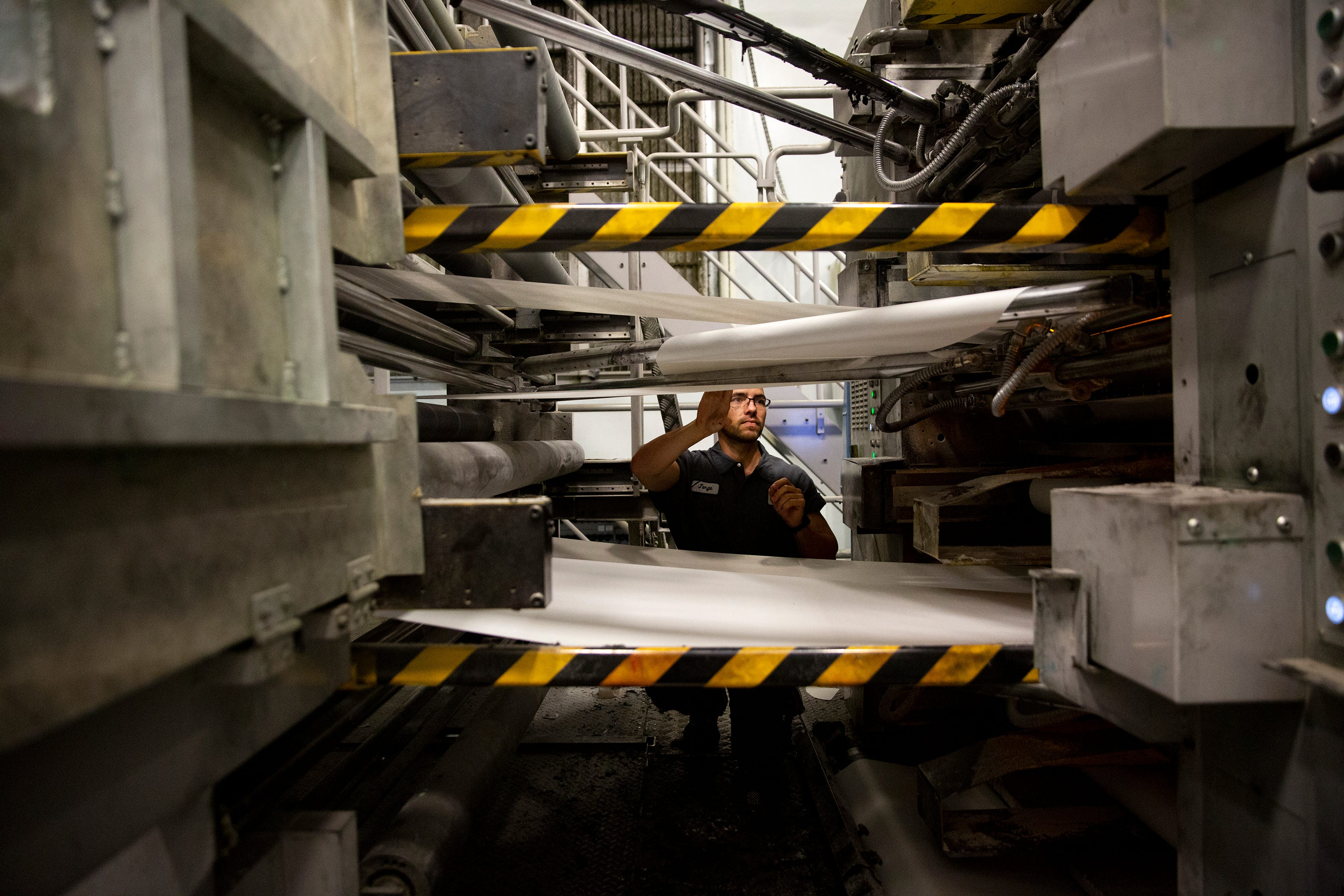 Press operator Yasniel Valdivia guides a kite, a leader used to thread paper through the press machines before a press run Wednesday, Feb. 12, 2020, at the Naples Daily News.