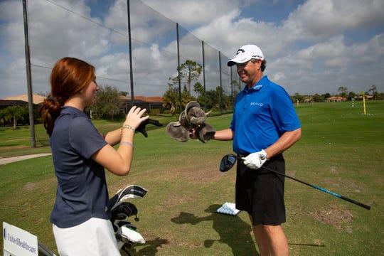 Sophie Shrader and professional golfer Lee Janzen chat before hitting golf balls, Thursday, Feb. 13, 2020, at the Lely Resort driving range.