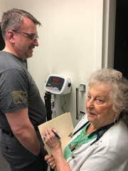 Barbara Wilson, who has volunteered at the Licking County Community Health Clinic for 27 years, monitors a patient's weight on Wednesday at the clinic.