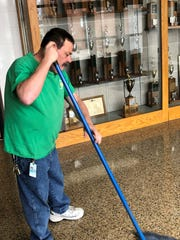 """Robert """"Boo"""" Hayden mops in front of the Newark Catholic trophy case in the main hallway at the high school. For nearly 24 years, he's watched Green Wave athletes fill that case, in addition to his numerous duties at the school."""