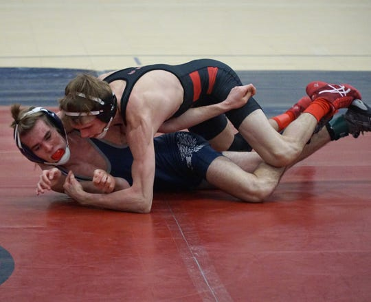 Farmington, left, and Churchill's 125 lbs. wrestlers compete on Feb. 12, 2020.