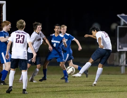 Osman David Martinez (17) kicks in a rebound to take a 1-0 lead in overtime during the first-round Class 5A state tournament boys soccer game between Fort Walton Beach and Washington at Booker T. Washington in Pensacola on Wednesday, Feb. 12, 2020.