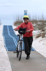 John Brauer finds the new dune walkovers easy and convenient to use during his stay at Pensacola Beach on Thursday. Later this month, the five-year effort to replace some of the dune walkovers on Pensacola Beach will come to an end