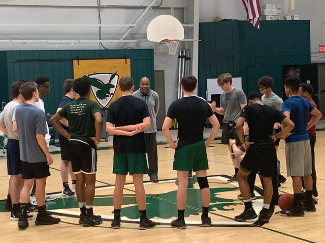 East Hill Christian boys basketball coach Samba Johnson (center) instructs his team during preparations for Panhandle Christian Conference tournament.