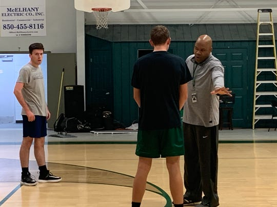 East Hill Christian boys basketball coach Samba Johnson (right) instructs his team during preparations for Panhandle Christian Conference tournament.
