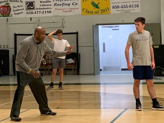East Hill Christian boys basketball coach Samba Johnson (left) instructs his team during preparations for Panhandle Christian Conference tournament.