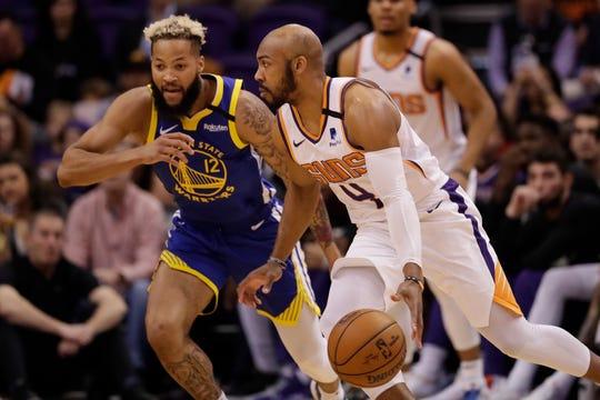 Phoenix Suns guard Jevon Carter (4) looks to pass as Golden State Warriors guard Ky Bowman (12) defends during the first half of an NBA basketball game, Wednesday, Feb. 12, 2020, in Phoenix. (AP Photo/Matt York)