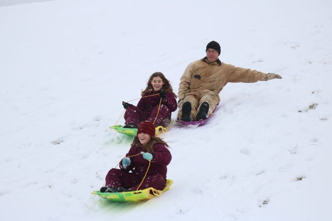 "Jami and Danica Schlotterer, both 9, spend the ""snow day"" off from school sledding with their father at Portage Park in Port Clinton on Thursday."