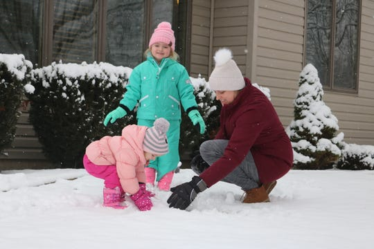 The Evans family, Olivia, Ella, and their mother Whitney, take advantage of the weather in Port Clinton on Thursday by building a snowman.
