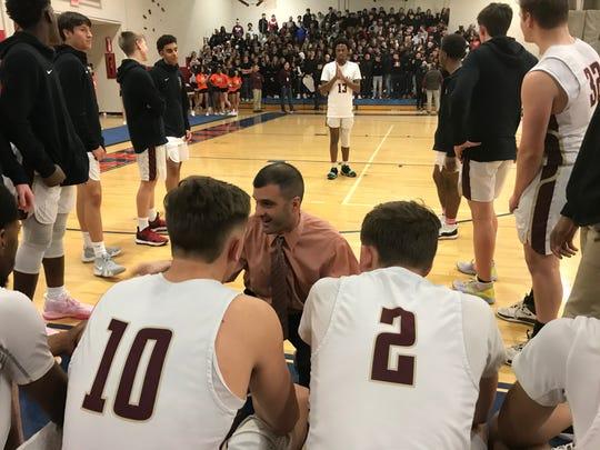 Arlington basketball coach Matt Hoyt talks with his players.