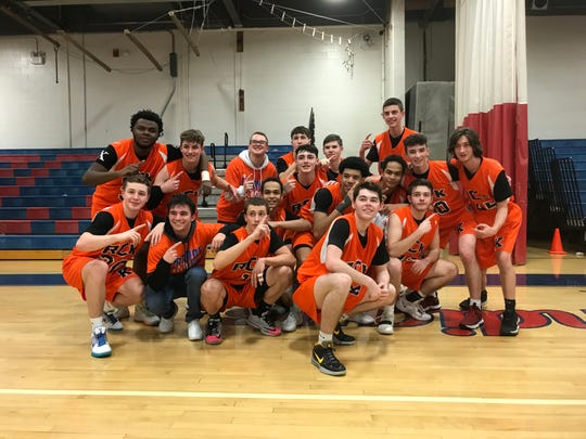 The Roy C. Ketcham High School boys basketball team poses after defeating Arlington 49-47 in its 'Orange Out' game. The Indians won their league title.