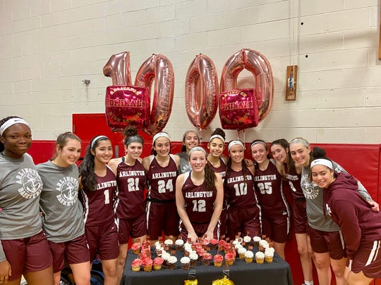 Arlington's Molly Stephens is flanked by teammates as they celebrate with cupcakes and balloons commemorating the senior eclipsing 1,000 career points on Wednesday.