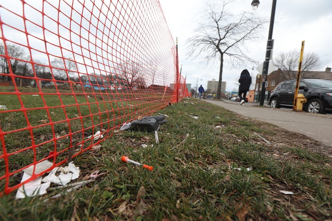 Pedestrians walk by a needle and discarded trash along the fencing for La Marketa at the International Plaza on N. Clinton Ave.