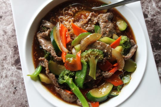 Sichuan Giants menu item 112, Beef Lass Fried Yellow ($15.50), is a mild beef and vegetable stew blanketingthin noodles.