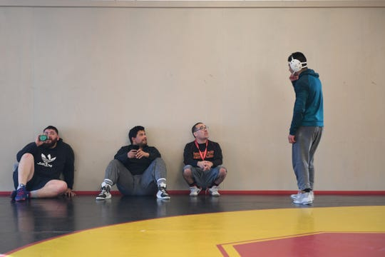 Coach Isaiah Jimenez (second from left) values Thompson's quiet leadership style that shows younger wrestlers the right way to practice and compete. Feb. 11, 2020.