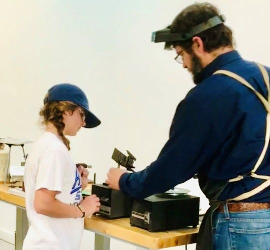 Famous spur maker Wilson Capron from Christoval shows a young student how to use engraving tools in a workshop held at the San Angelo Museum of Fine Arts.