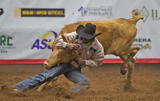 Tory Johnson competes in the steer wrestling event at the San Angelo Stock Show and Rodeo on Wednesday, Feb. 12, 2020.