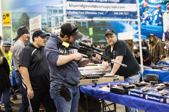 A vendor looks on as a customer handles a scoped assault rifle at a 201825 gun show.  A majority of vendors, including the one pictured, owned retail stores around Virginia and traveled to the Richmond show with a smaller selection to sell. (Photo by Erin Edgerton)