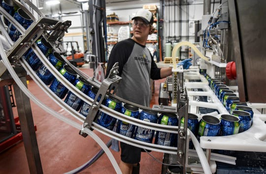 Matt Studer watches as empty cans are prepared for filling May 24, 2017, on the first day of production at the new 10,000-square-foot Beaver Island Brewing Co. facility in St. Cloud. T