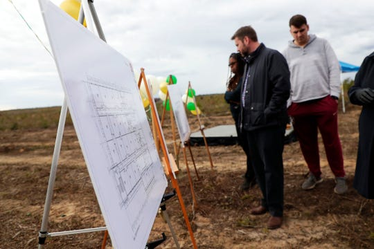 People look at floor plans and renderings for the charter school, Tallahassee Classical, during a groundbreaking ceremony for the future grounds of the school.