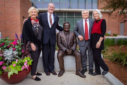 Jeane Thrasher, left, FSU President John Thrasher, Penn State President Eric Barron, and Molly Barron, pose for a photo with the statue honoring Barron outside of the new Earth, Ocean, Atmospheric Science Building.