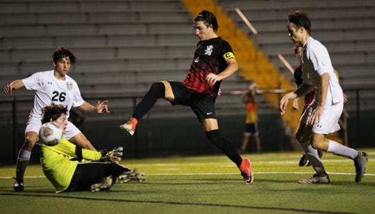 Leon senior Henry Regalado one-times a goal past Lincoln keeper Aiden Reiding as Leon's boys soccer team beat Lincoln 4-2 during a Region 1-6A quarterfinal playoff game on Feb. 12, 2020.