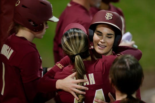 Florida State University's Chloe Culp (28) is hugged by her teammates in the dugout after scoring a home run during a game between Florida State and Florida A&M University at JoAnne Graf Field Wednesday, Feb. 12, 2020.