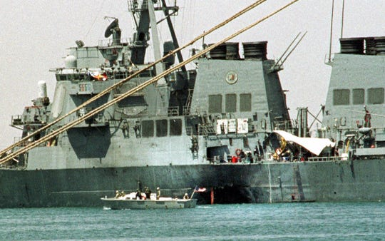 A small boat guards the USS Cole on Friday, Oct. 20 2000, in Aden, Yemen. A federal judge on Wednesday March 14, 2007, found Sudan liable for the attack on the now-repaired Navy destroyer, but said he would need time to study all the evidence and documentation to determine the amount of damages the families deserve.