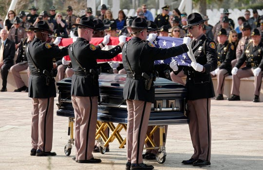 Florida Highway Patrol officers fold the American flag Thursday, Feb. 13, 2020, from the casket of slain Florida Highway Patrol Trooper Joseph Bullock at Sarasota National Cemetery before presenting it to family members.