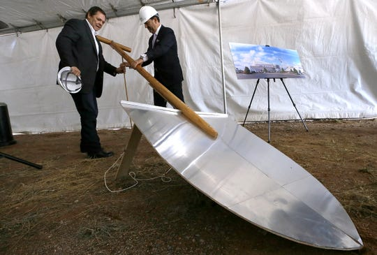 Paul Foster, left, owner of Franklin Mountain Investments Limited Partnership, and Million Air CEO Roger Woolsey wrangle a giant shovel during the groundbreaking ceremony for the Million Air jet terminal being built at the El Paso International Airport.