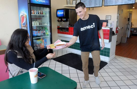 Chris Ekblad, 22, co-owner of Ameci Pizza Kitchen, serves a spaghetti meal to Melissa Mendoza at the chain's Santa Paula location. Ekblad is one of four brothers who took over the restaurant in November 2019, about a year after they bought the chain's Camarillo location.