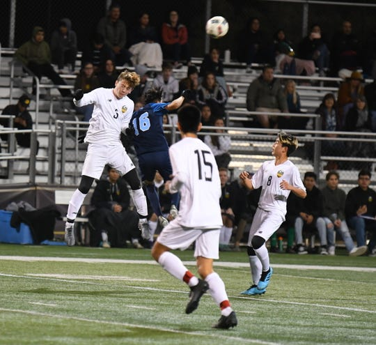 Camarillo's Ernesto Rodriguez (16) leaps for an aerial challenge against Thousand Oaks in the first round of the CIF-Southern Section Division 3 boys soccer playoffs on Wednesday night at Cal Lutheran University. Camarillo won, 4-0.