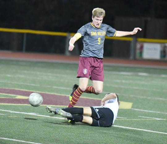 Simi Valley defender Dylan Studer is tackled by Pacifica forward Jorge Arrellano in the first round of the CIF-Southern Section Division 2 boys soccer playoffs on Wednesday night. Pacifica won, 2-0.