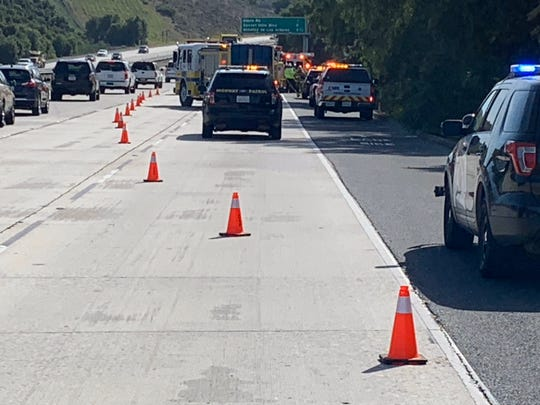 First responders work along southbound Highway 23, south of Tierra Rejada Road, where a car ran off the road and overturned late Thursday morning near Moorpark.