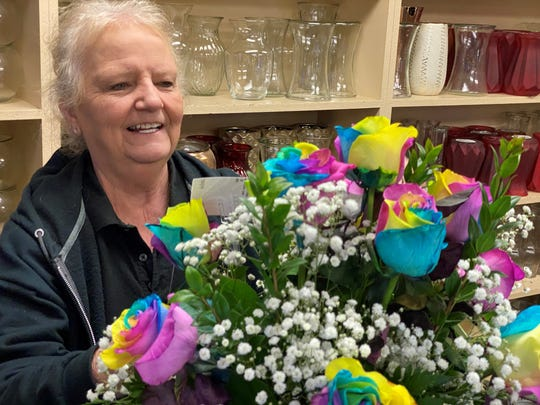 Peter Perkens floral designer Betty Land arranges a tie-dyed bouquet for a Valentine's Day customer in Visalia.